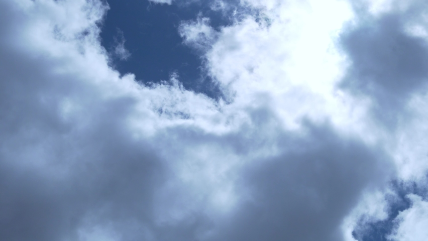 Puffy Cumulus Clouds Shining Sun in a Blue Sky, Time Lapse. Background of Flying Fluffy Sun Clouds, Sun Rays and Blue Sky. Nature, Summer Sunny Cloudy Day. Cloud Cover. Air, Atmosphere, Ozone Layer.