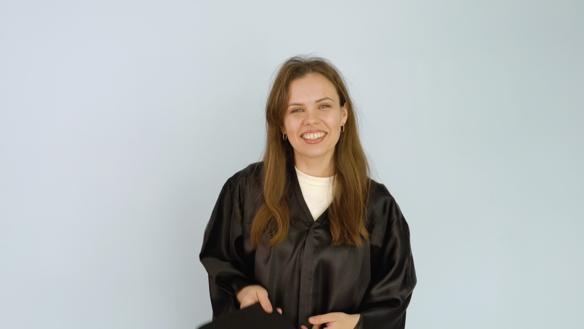 Young caucasian female student in a black robe lightly throws a square hat with a tassel up and catches.White background | Shutterstock HD Video #1071013753