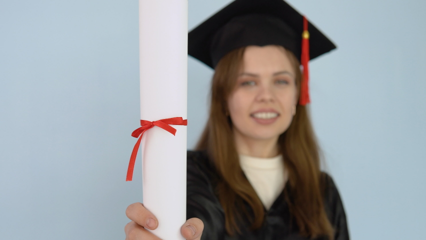 Young female student in a black gown and a master's hat holds in her hands in an upright position a diploma of higher education. A university graduate dances with a diploma in her hands and sneezes | Shutterstock HD Video #1071013759