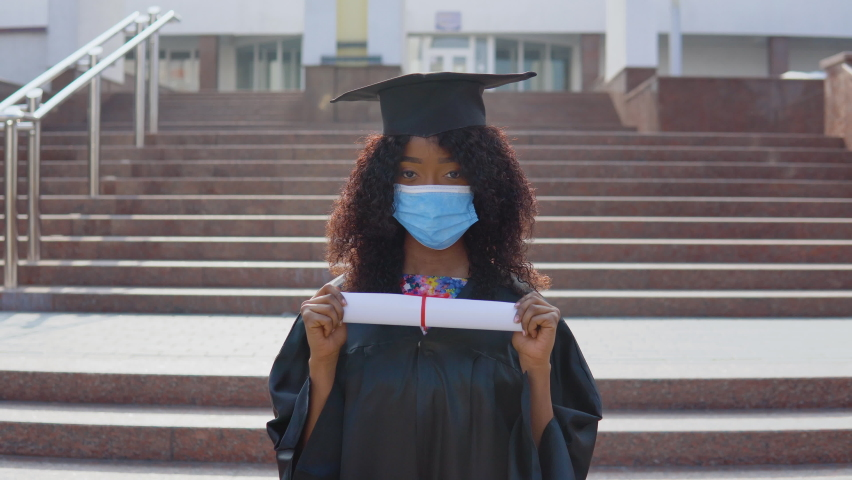 Young african american female graduate standing in front of the camera with a diploma in her hands. The student has a protective medical mask. She stands on the stairs outside. | Shutterstock HD Video #1071013801