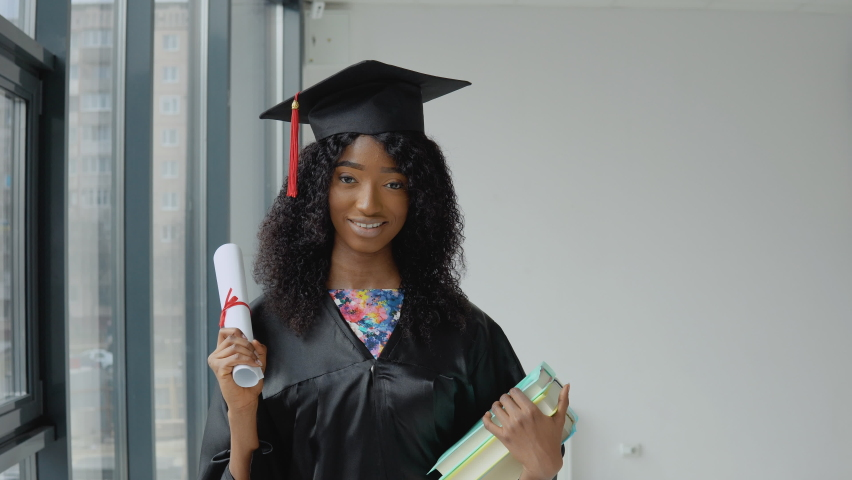 Young african american female graduate standing in front of the camera with a diploma and books in her hands. The student is wearing a black robe and a square master's hat. | Shutterstock HD Video #1071013804