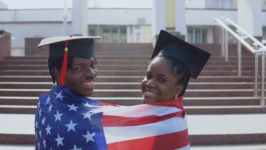 African American man and woman standing side by side with their backs to the camera in square hats of graduate students with the USA flag on their shoulders. Looking to the camera | Shutterstock HD Video #1071013807