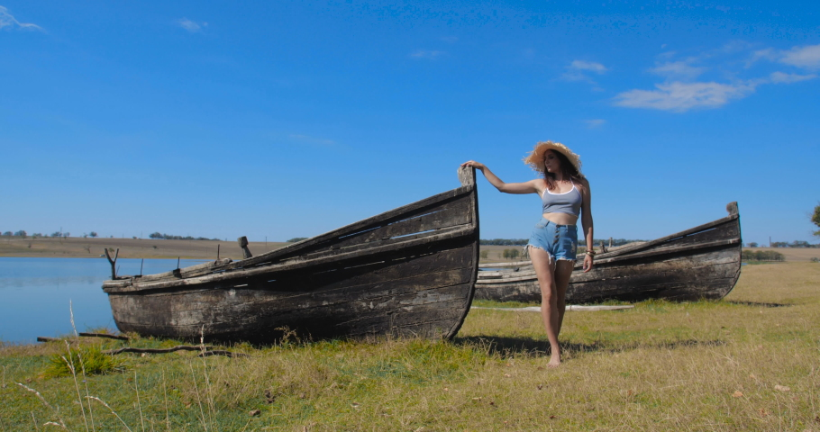 Attractive young woman in a straw hat and denim shorts walking near abandoned wooden boats on a shore on a hot sunny day. Tracking shot 4k 50 fps slow motion | Shutterstock HD Video #1071014050