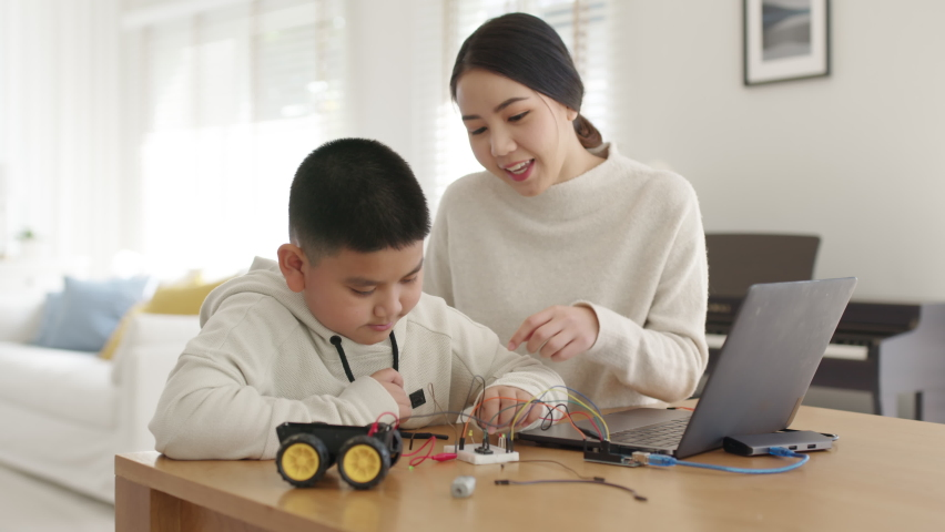Young asia student remotely learn online at home with parent in coding robot car and electronic board cable in STEM, STEAM, mathematics engineer science technology computer code in robotics for kids. | Shutterstock HD Video #1071014089