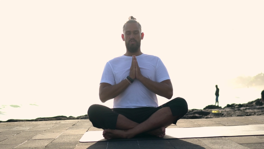 Caucasian male sitting in lotus namaste pose and talking mantras during morning pray, young man training mindfulness and own concentration during asana practice outdoors | Shutterstock HD Video #1071014347