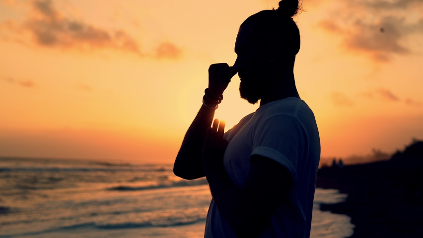 Side view of tranquil male yogi praying during sundown meditation time at coastline, man keeping healthy lifestyle searching soul calmness keep praying at seashore beach | Shutterstock HD Video #1071014350