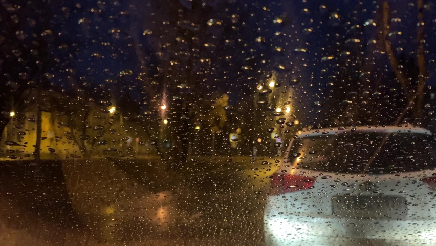 Water drops background. A drop of rain is flowing on the windshield of a car. Natural pattern of raindrops. Abstract shot of raindrops on glass. Night time outside the window. Selective focus.  | Shutterstock HD Video #1071014452