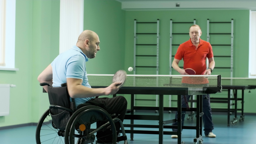 A man in a wheelchair plays ping pong. People with disabilities play table tennis. Rehabilitation of the disabled. Paralympic sport. | Shutterstock HD Video #1071014572