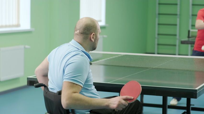 A man in a wheelchair plays ping pong. People with disabilities play table tennis. Rehabilitation of the disabled. Paralympic sport. | Shutterstock HD Video #1071014578