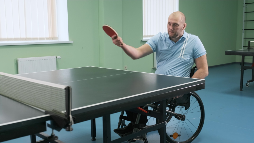 A man in a wheelchair plays ping pong. People with disabilities play table tennis. Rehabilitation of the disabled. Paralympic sport. | Shutterstock HD Video #1071014593