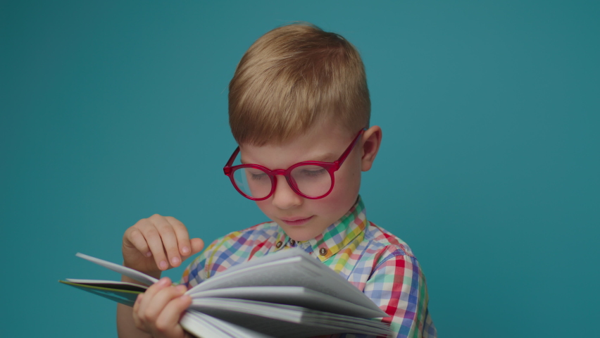 Preschool boy wearing eyeglasses reading paper book holding textbook in hands standing on blue background. Happy school kid studying with book. | Shutterstock HD Video #1071014953