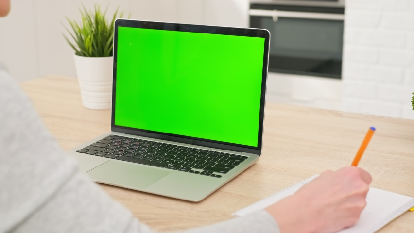 Girl uses green screen chroma key laptop for learning, writes down useful information. distance learning, e-education, e-learning, homeschooling concept. close-up over shoulder POV | Shutterstock HD Video #1071015412