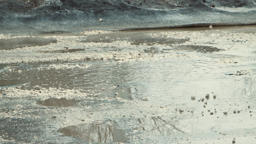 Close-up car driving on a bad road with cracks, muddy puddles and pits. A crumbling road with potholes. Old asphalt pavement made in violation of technology. Taxpayer money is wasted. | Shutterstock HD Video #1071015511