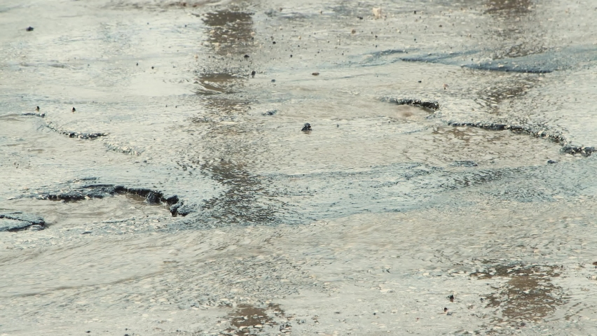 Fast driving of car wheels on a bad road with muddy puddles, holes and cracks. A crumbling road with potholes. Old asphalt pavement made in violation of technology. Taxpayer money is wasted. | Shutterstock HD Video #1071015514