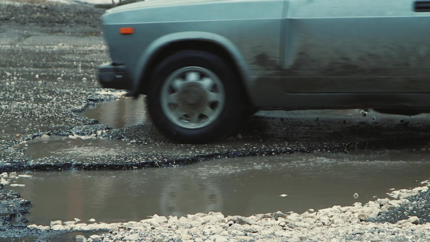 Cars move slowly in close-up on a road with muddy puddles and pits. A crumbling road with potholes. Old asphalt pavement made in violation of technology. Taxpayer money is wasted. | Shutterstock HD Video #1071015526