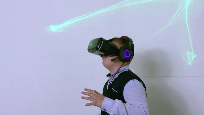 The boy in the augmented reality helmet dances cheerfully, waves his arms. Close-up of a child of Caucasian ethnicity with a vr headset on his head in virtual space on a white background. | Shutterstock HD Video #1071015538