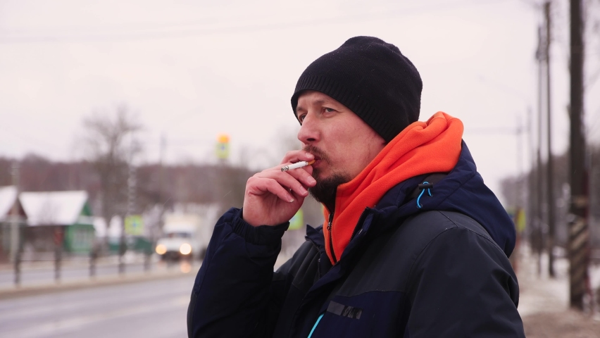 A man smokes on the side of the road looking at the road with cars. A male in a warm jacket is standing on the highway and waiting for his car. In the background, trucks and cars drive by in defocus. | Shutterstock HD Video #1071015565