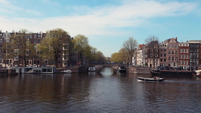 Boats circulate in opposite directions on the Amstel River next to the Magere Brug bridge. | Shutterstock HD Video #1071015643