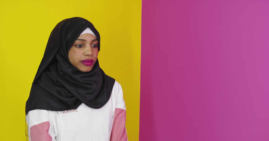 Beautiful african american girl wearing muslim hijab over color background  | Shutterstock HD Video #1071015769