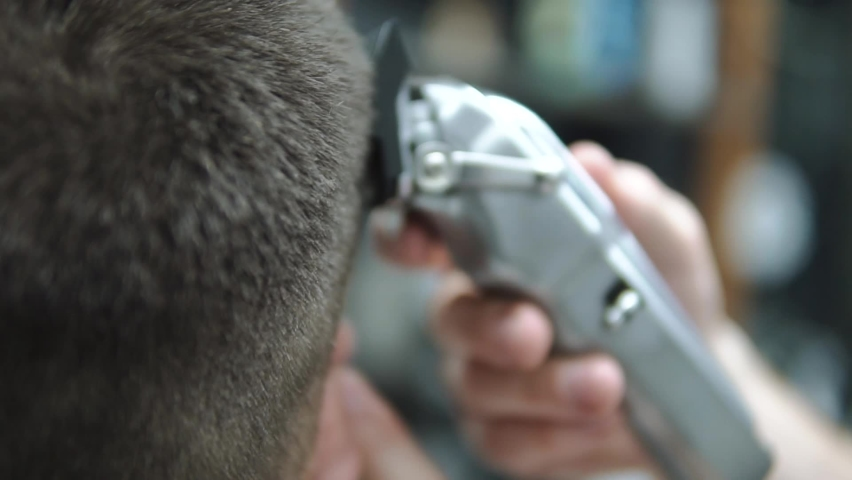Male haircut with electric razor. Close up of hair trimmer hairstyle. Barber makes haircut for client at the barber shop by using hairclipper. Man hairdressing with electric shaver. Handheld shot. | Shutterstock HD Video #1071015895