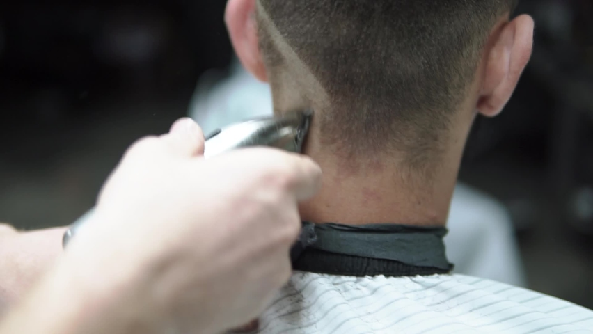 Male haircut with electric razor. Close up of hair trimmer hairstyle. Barber makes haircut for client at the barber shop by using hairclipper. Man hairdressing with electric shaver. Handheld shot. | Shutterstock HD Video #1071015907
