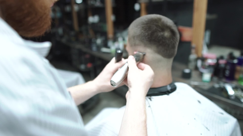 Male haircut with electric razor. Close up of hair trimmer hairstyle. Barber makes haircut for client at the barber shop by using hairclipper. Man hairdressing with electric shaver. Handheld shot. | Shutterstock HD Video #1071015910