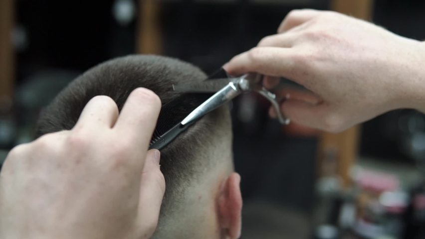 Close-up of barber cuts the hair by scissors at barbershop. Hairdresser's hands at working process. Barber making haircut of attractive bearded man in barbershop. Hairdresser at work. Beauty saloon. | Shutterstock HD Video #1071015994