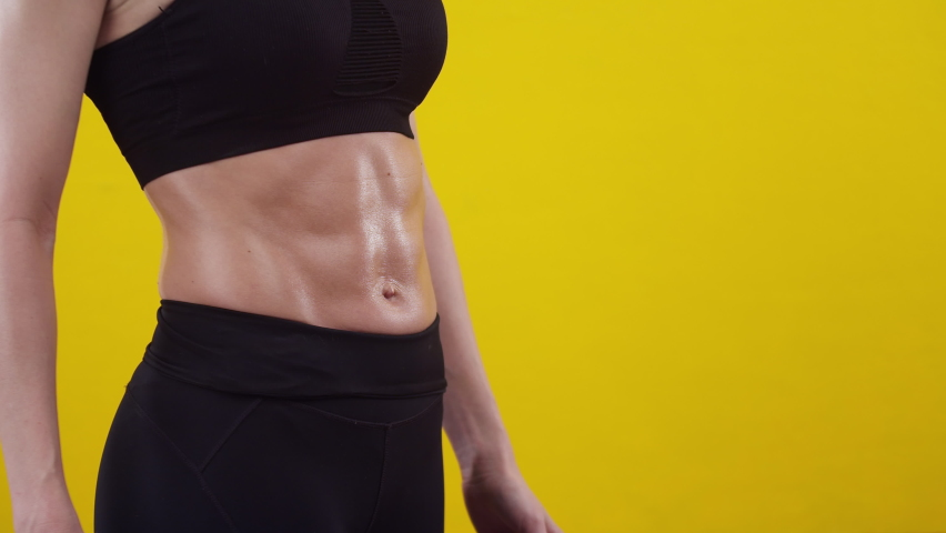 Woman in a sports uniform shows on muscular belly with hands in the studio, close-up. Woman shows muscles of the abdomen on an orange background. Concept of sports lifestyle and training. | Shutterstock HD Video #1071016027