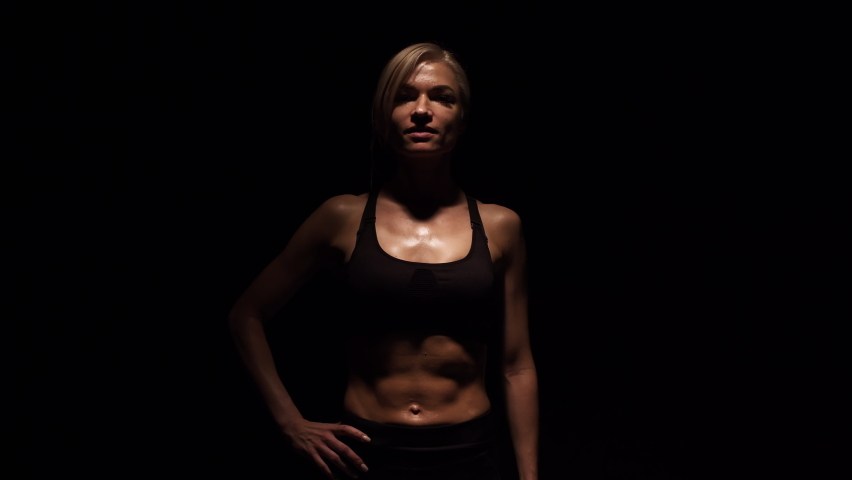 Sports woman emerges from darkness and puts hand on waist. Muscular woman walks out from the darkness in the studio. | Shutterstock HD Video #1071016030