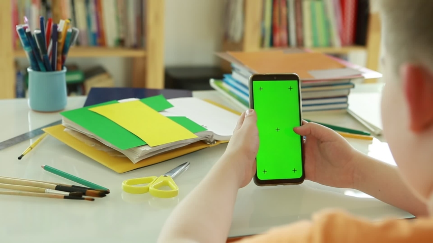 An elementary school student uses online videos to learn. Phone with Green Screen and Chroma Key in the hands of a Primary school student. Schoolboy Scroll Up Cellphone by Finger.  | Shutterstock HD Video #1071016117
