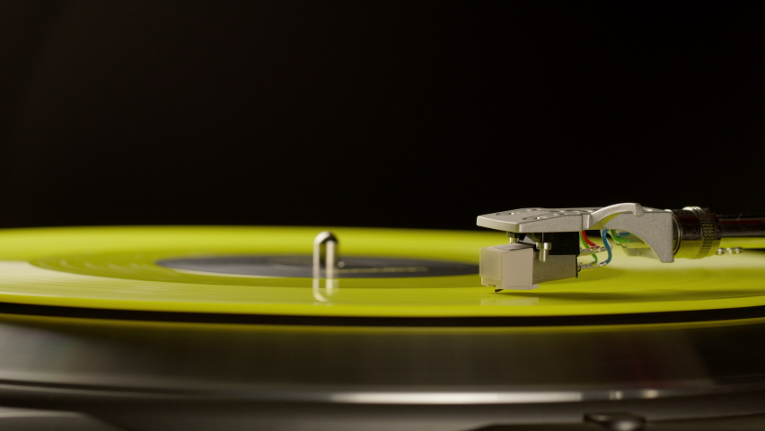 Yellow vinyl record spinning on modern turntable playing music. Close-up, black background. Concept of vinyl record collectors, vinyl lovers, top records, cool again, old-school, summer. Copy space | Shutterstock HD Video #1071016690