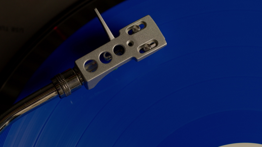 Close-up tonearm placed on blue vinyl record spinning on modern turntable playing music. Top view. Concept of record collectors, vinyl lovers, home audio, cool again, old-school. Copy space | Shutterstock HD Video #1071016693