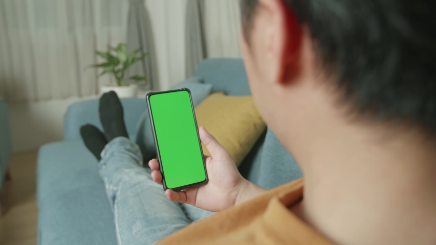 Male Celebrating While Using Smartphone With Green Screen Display In Living Room  | Shutterstock HD Video #1071016780
