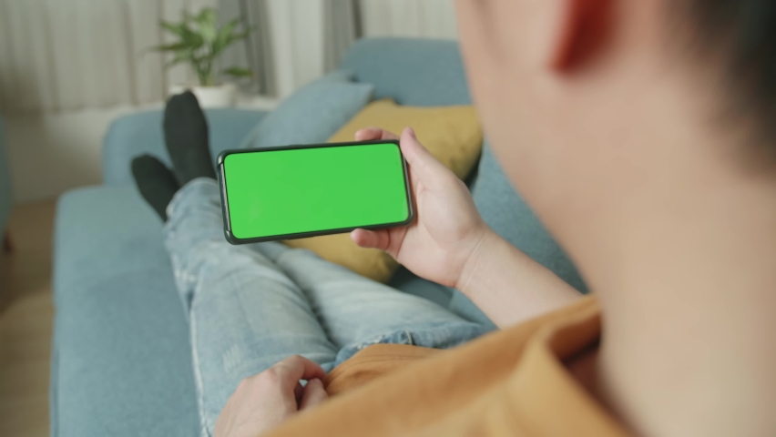 Male Using A Smartphone With Green Screen Mock Up Display At Home Living Room While Lying On Sofa  | Shutterstock HD Video #1071016783