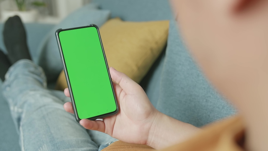 Male Video Call Smartphone With Green Screen Mock Up Display At Home Living Room  | Shutterstock HD Video #1071016789