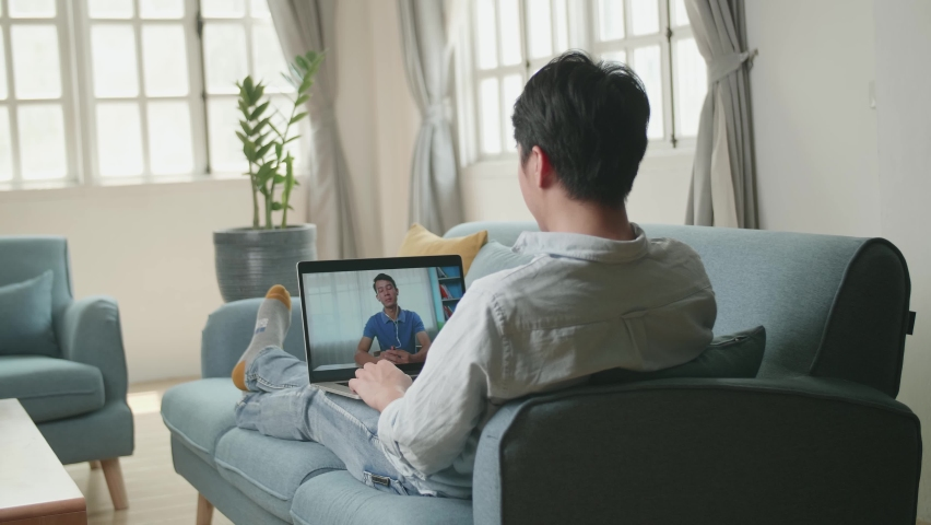 Man Greeting With Colleagues In Video Conference From Laptop At Home Living Room   Shutterstock HD Video #1071016810