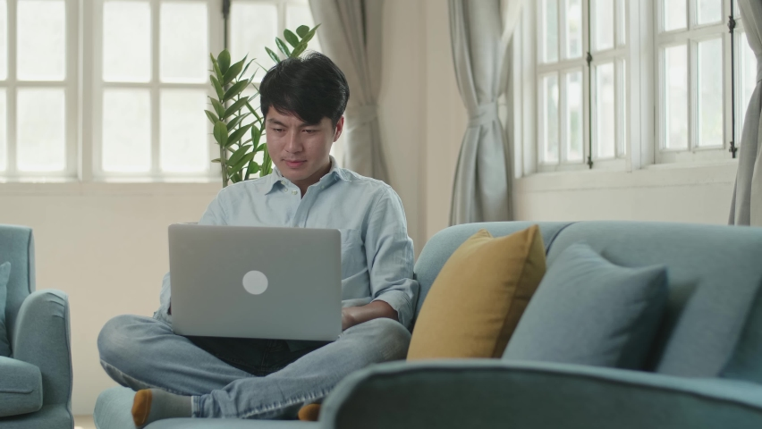Man Sitting Sofa And Use Laptop Computer In Living Room   Shutterstock HD Video #1071016828