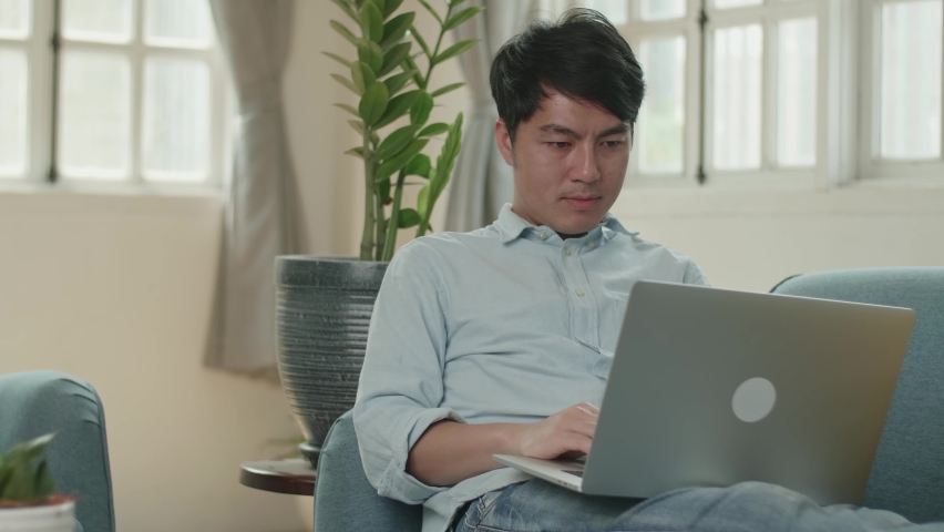 Male Use Laptop Computer And Celebrating In Living Room    Shutterstock HD Video #1071016831