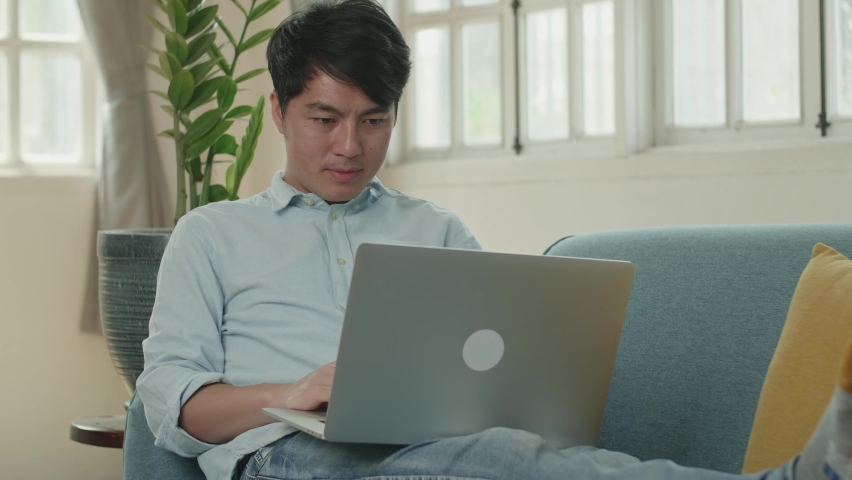 Asian Male Use Laptop Computer And Smiling In Living Room While Lying On Sofa  | Shutterstock HD Video #1071016837