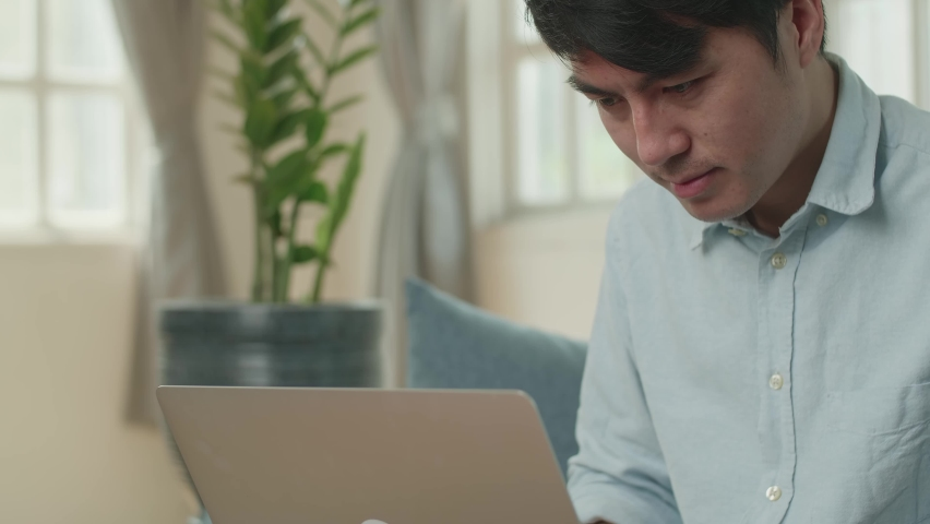 Asian Male Working On Laptop And Smiling At Living Room  | Shutterstock HD Video #1071016840