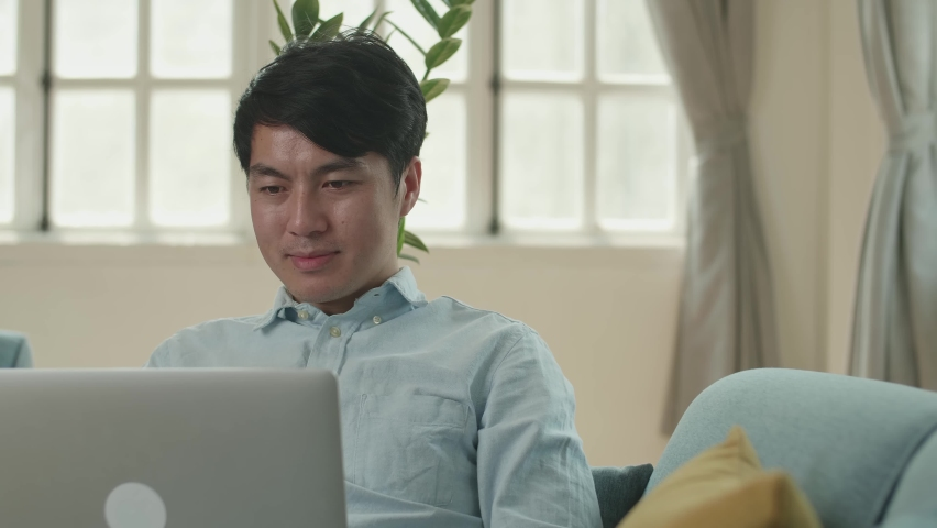 Asian Male Use Laptop Computer In Living Room While Lying On Sofa    Shutterstock HD Video #1071016843