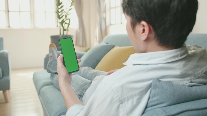 Male Video Call While Using Smartphone With Green Screen Display In Living Room | Shutterstock HD Video #1071016882