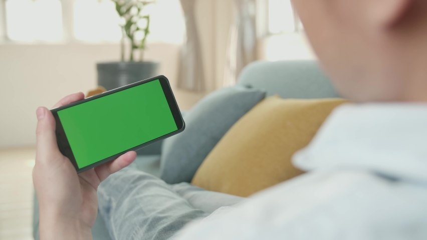 Male Video Call While Using Smartphone With Green Screen Display In Living Room | Shutterstock HD Video #1071016885