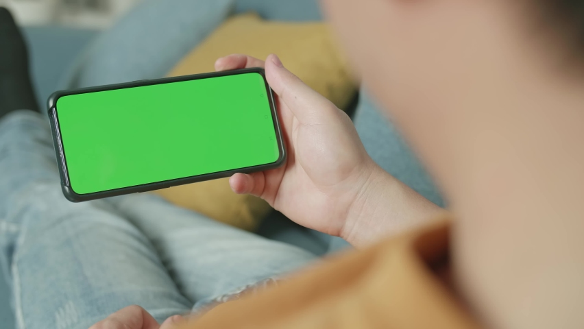 Male Using A Smartphone With Green Screen Display At Living Room While Lying On Sofa | Shutterstock HD Video #1071016888