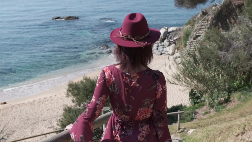Woman with a purple dress and hat going to the beach in a bright summer day | Shutterstock HD Video #1071016930