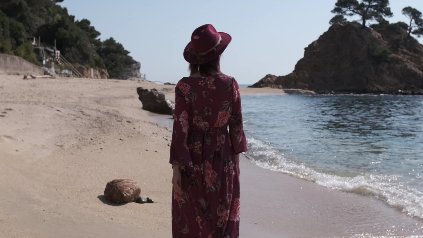 Young woman in a lonely beach with purple dress and hat walking on the sand | Shutterstock HD Video #1071016933