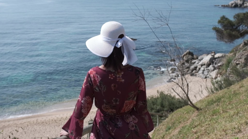 Young woman going to the beach wearing a white hat | Shutterstock HD Video #1071016942