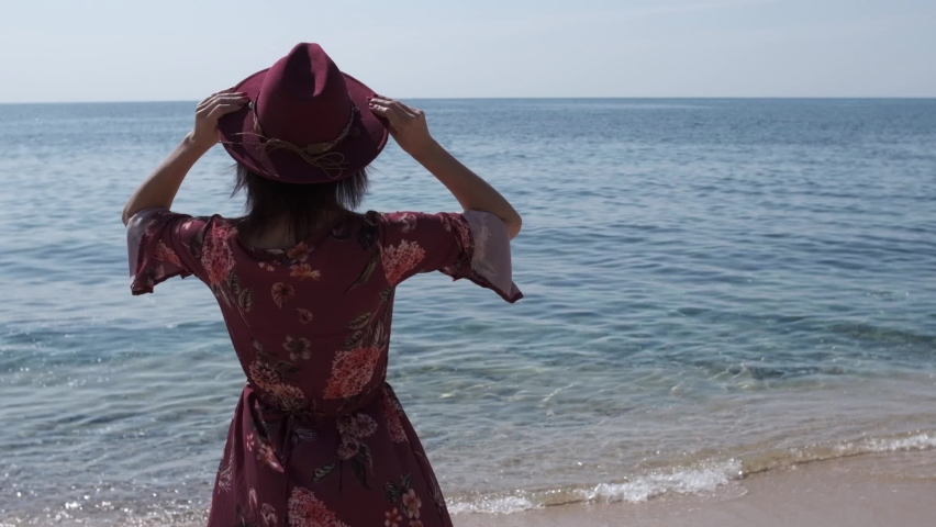 Young woman with purple dress and hat in a sunny day in front of the beach | Shutterstock HD Video #1071016945