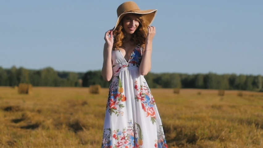 Beautiful red-haired girl in a white dress and hat stands against the background of a field and haystacks. Young woman at sunset on the background of nature | Shutterstock HD Video #1071017164