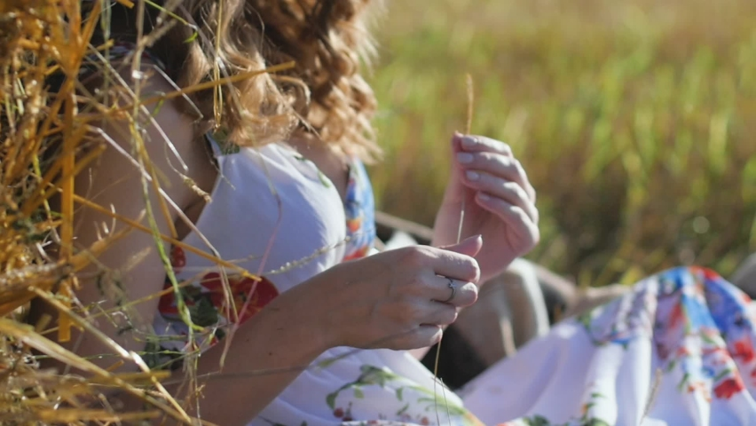 Close-up portrait of attractive young redhead woman sitting near haystack, woman smiling and enjoying nature and life | Shutterstock HD Video #1071017173